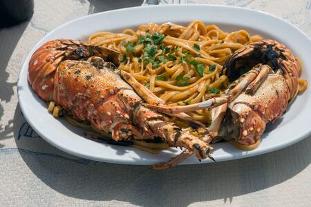 Delicious lunch by the sea. A white plate of spaghetti with huge lobsters on the grill. Travel to Santorini, Greece. Old port of Fira. Archivio Fotografico