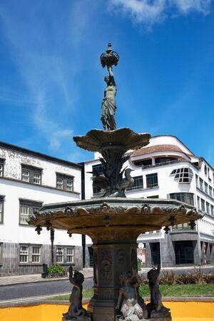 Cast iron fountain in Vasco da Gama Square in the historic center of Ponta Delgada.  Fountain 'Vasque or Water Tower' . Sculptor Hubert Lavigne. Island San Miguel, Azores. Sights of Ponta Delgada.