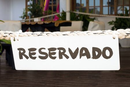 On a thick rope in a Spanish restaurant on the island of Mallorca is a white Reservado sign. The restaurant is closed for special services. VIP guests.