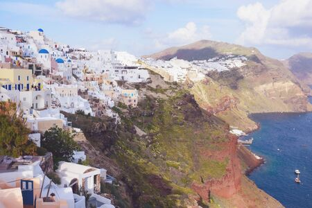 Beautiful island of Santorini, Greece. Traditional white greek houses against the backdrop of the sea. The city of Oia on the island of Santorini. Greek journey. Sunset.