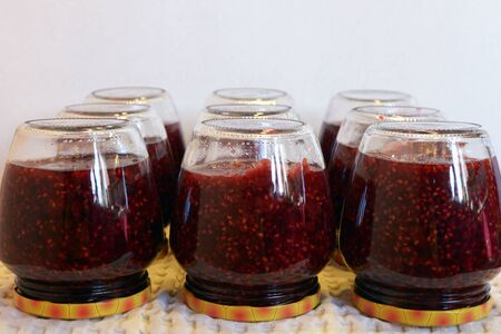 Jars with raspberry jam on a white towel. We make raspberry jam at home. Canning. Harvesting confiture.