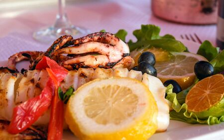 Grilled squid, lemon, olives and wine. Romantic dinner for two by the sea. Warm summer evening.