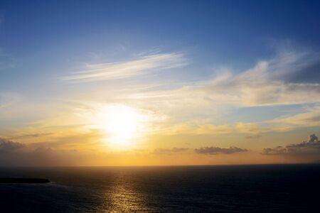De felle zon tegen de achtergrond van wolken, lucht en zee in de schemering. Zonsondergang op zee.