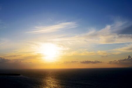 The bright sun against the background of clouds, sky and sea at dusk. Sunset at sea.