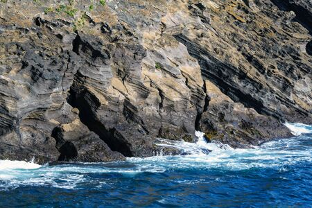 Waves of the turquoise sea crash against rocks of volcanic origin on the island of San Miguel, Portugal. Sea element. Travel to the Azores. Stock fotó
