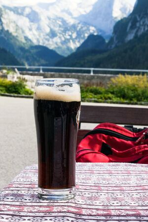 A glass of delicious dark Austrian beer against the backdrop of the European Alps in a restaurant. Lunch while traveling. Gosauzen Region, Austria.