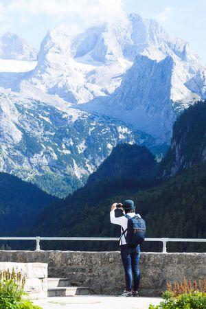 Hallstatt, Austria, September 2019. A young Chinese girl makes a selfie on a background of European Alps. Gosauzen Region, Austria Stok Fotoğraf