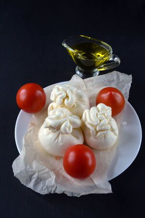 Burrata, italian fresh cheese made from cream and milk of buffalo or cow on a black background. Close-up. Three heads of cheese with tomatoes and olive oil.