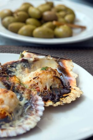 Baked scallops with cheese and spicy sauce. Delicate clam is a real pleasure. Romantic dinner at a Spanish fish restaurant. Mallorca Island, Spain.