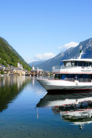 Hallstatt, Austria, September 2019. Famous mountain village in the Austrian Alps on a warm autumn day. Pleasure boat on the lake. Reflection. Traveling to the picturesque places of Austria.