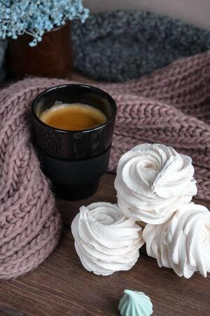 Handmade apple white homemade marshmallows on a brown plate and coffee in a black mug on a wooden table. Sweet zephyr and aromatic coffee. Archivio Fotografico - 138943652