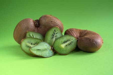 Big ugly vegetable organic kiwi on a green background. Sweet fruit slices. Ugly food concept.