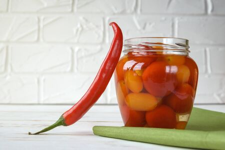 Fermented foods. Salted tomatoes in a glass jar on a white background. Vegetarian food. Super food.