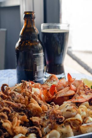 Fried seafood platter. Shrimp, squid, fish and vegetables in spicy sauce. Lunch at an old fish restaurant on Cyprus. Glass and a bottle with dark beer in the background. Gastronomic journey. Banque d'images