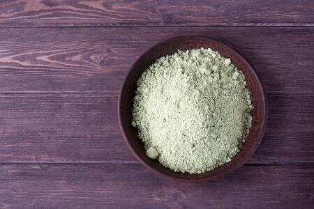 Pumpkin seed flour in a clay plate on a dark wooden background.