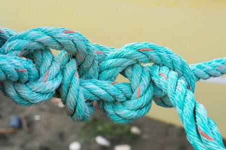 Vieille corde verte nouée sur fond jaune. Nouer. Concept de problème insoluble
