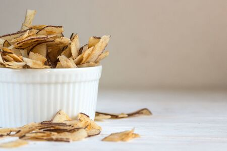 Delicious crispy coconut chips with salted caramel in a white plate on a white background. Natural product made from coconut pulp. Useful snack for a snack. The concept of proper nutrition.
