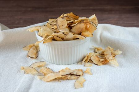 Delicious crispy coconut chips with salted caramel in a white plate. Natural product made from coconut pulp. Useful snack for a snack. The concept of proper nutrition.