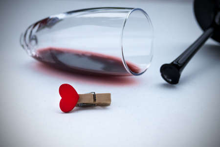 Small red heart in a broken wine glass. Broken love, depression and hopelessness concept.
