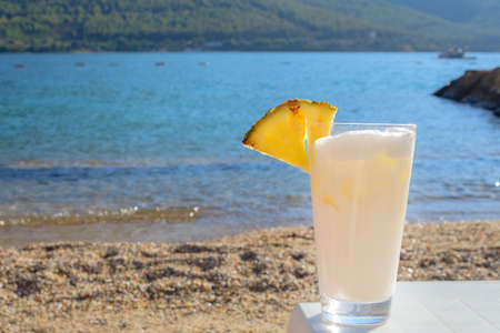 Delicious Pina Colada cocktail in a glass with a slice of pineapple on the background of the sea. Rest by the sea. Summer travel.