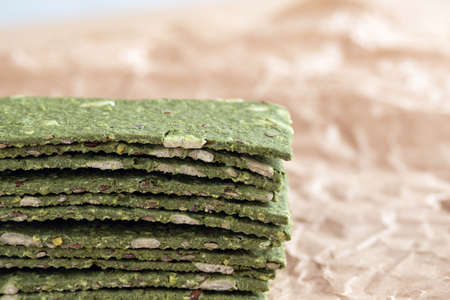 Vegetarian chips with seaweed. Crispy chips with spirulina, flax seeds, ginger and wasabi on craft paper. Marine multi-snacks. Superfood. The concept of proper nutrition.