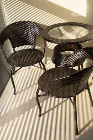 Brown chairs and a table on the balcony in the rays of bright light. A place to rest.