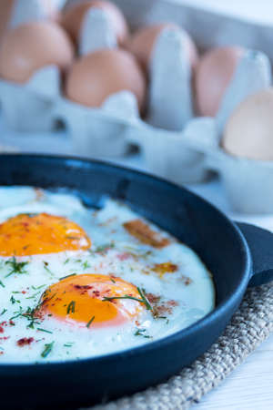 Scrambled eggs in a black cast iron pan and eggs in a tray. Light protein breakfast.