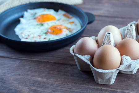 Chicken eggs in a cardboard tray on the background of scrambled eggs in a black cast-iron pan and eggs in the tray.