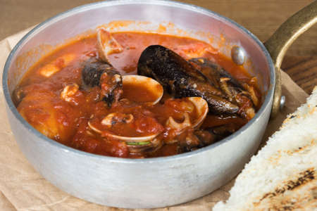 Delicious hearty lunch at a fish restaurant. Tuscan tomato soup with seafood Cacciucca. Cacciucco is a mixture of fish broth, red wine and tomato sauce.