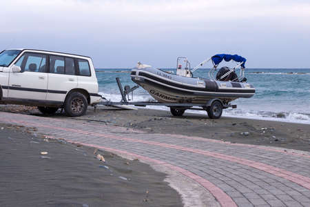 Cyprus, Limassol, February 2020. A white jeep tows a rubber inflatable boat on the seashore.