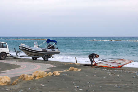 Cyprus, Limassol, February 2020. A girl in a black suit is getting ready to go windsurfing. Water sailing sport.