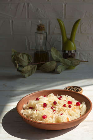 Sauerkraut with cranberries in a brown clay plate on a wooden background. Fermented vegetables. Super product for proper nutrition. Reklamní fotografie