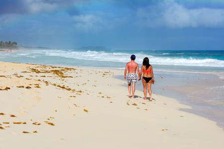 Dominican Republic, Punta Cana, December 2018. A man and a woman walk along the ocean shore holding hands. Paradise Island. Romantic trip.