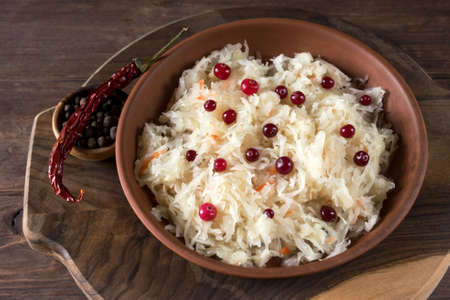 Sauerkraut with cranberries in a brown clay plate on a wooden background. Fermented vegetables. Super product for proper nutrition. View from above.