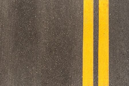 Black asphalt road texture with marking background. Double yellow line on asphalt road.