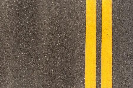 Schwarze Asphaltstraßenbeschaffenheit mit Markierungshintergrund. Doppelte gelbe Linie auf Asphaltstraße.