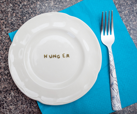 starvation: A symbolic word hunger written with macaroni on a whitel plate Stock Photo