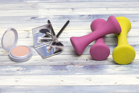 Womanly Beauty kit: makeup tools including the powder, the mirror and brushes with colorful fitness weights for workout.