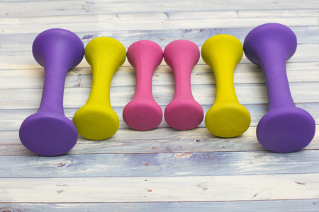 Female sport kit: Yellow, pink and purple workout weights on a blue wooden background Stock Photo