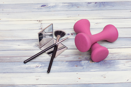 Womanly Beauty kit: makeup tools including the mirror and brushes with colorful fitness weights for workout.