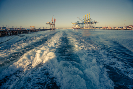 rapidly: Rapidly moving away from the industrial cargo port terminal with freight ships and cranes. Stock Photo