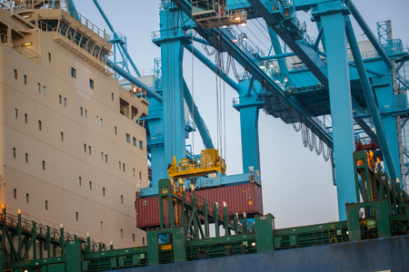 Container freight ship with working cranes in the industrial cargo port terminal Stock Photo