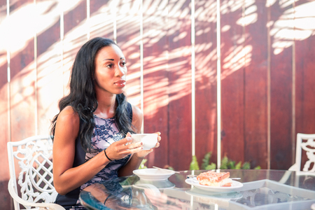 Pensive dark skinned woman having breakfast at the table on the