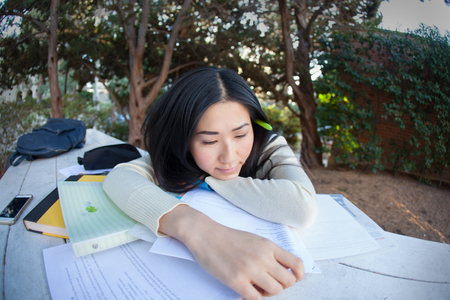 Sad young Asian girl laying on a pile of books and papers