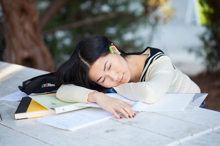 Beautiful teenage girl sleeping on notebooks in the park