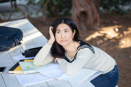 Sad and bored girl student lying in a pile of books Stock Photo