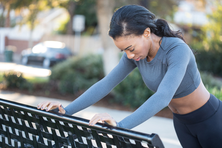 Beautiful female athlete working out at the bench in the city pa