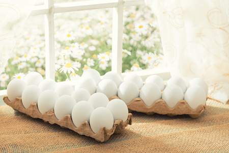 Easter shopping theme: white eggs in an egg crate on the window in a sunny day