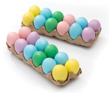 Vibrant Easter eggs in a crate on a seamless white background Stock Photo
