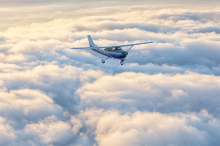 Small single engine airplane flying in the gorgeous sunset sky